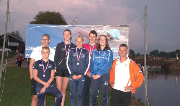 Links vooraan Storm Boxum en naast hem zusje Fay. Met andere medaillewinnaars van het OC Drachten en, rechts, trainer Henri Koek.