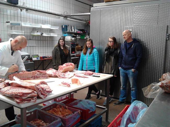 Slager Hatzmann is aan het werk. In lichtblauwe jas kijkt Simone Stronkhorst toe. Rechts van haar zus Annemiek en vader Tim.