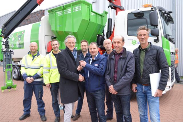 Wethouder Verlaan (3e van links) bij de vrachtwagen waarmee de containers worden geleegd.