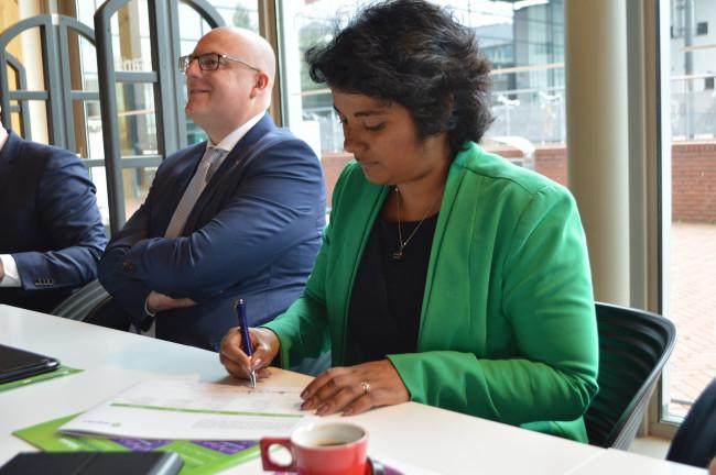 VVD-wethouder Irene Korting van economische zaken ondertekent het coalitieakkoord.