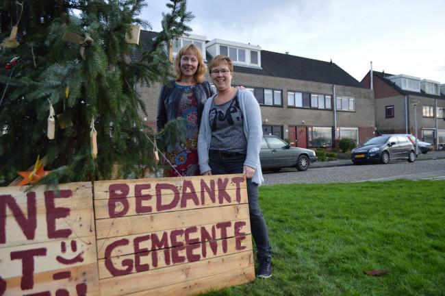 De buurvrouwen Karin Spekkink en Yvonne de Bree bij de kerstboom.