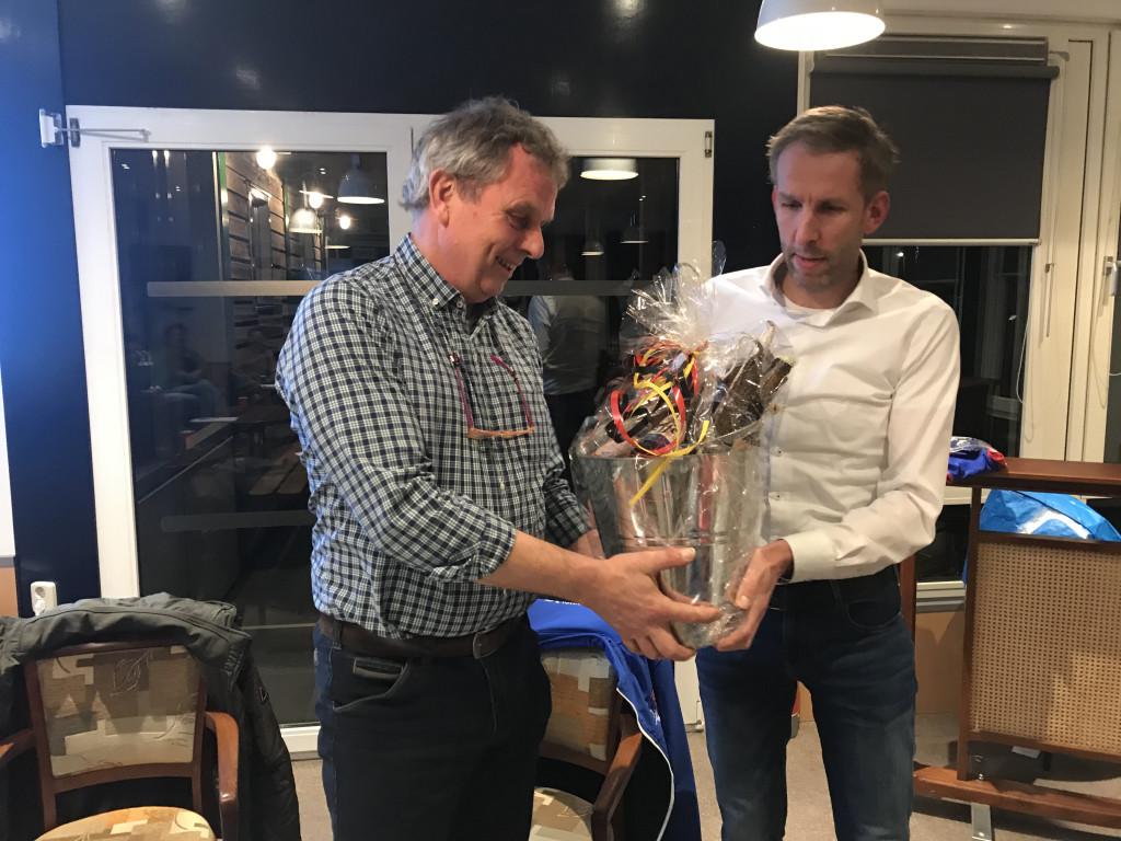 Voorzitter Jan Jonkers (l) ontvangt een afscheidscadeau van secretaris Edwin Knol (r) tijdens de jaarvergadering.