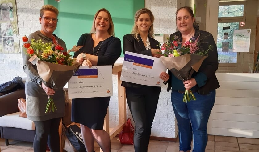 Rabobankmedewerkers Sandra Gilsing en Nienke Visser overhandigen twee cheques aan korfbalvereniging De Corridor   | Fotonummer: e9c8fc