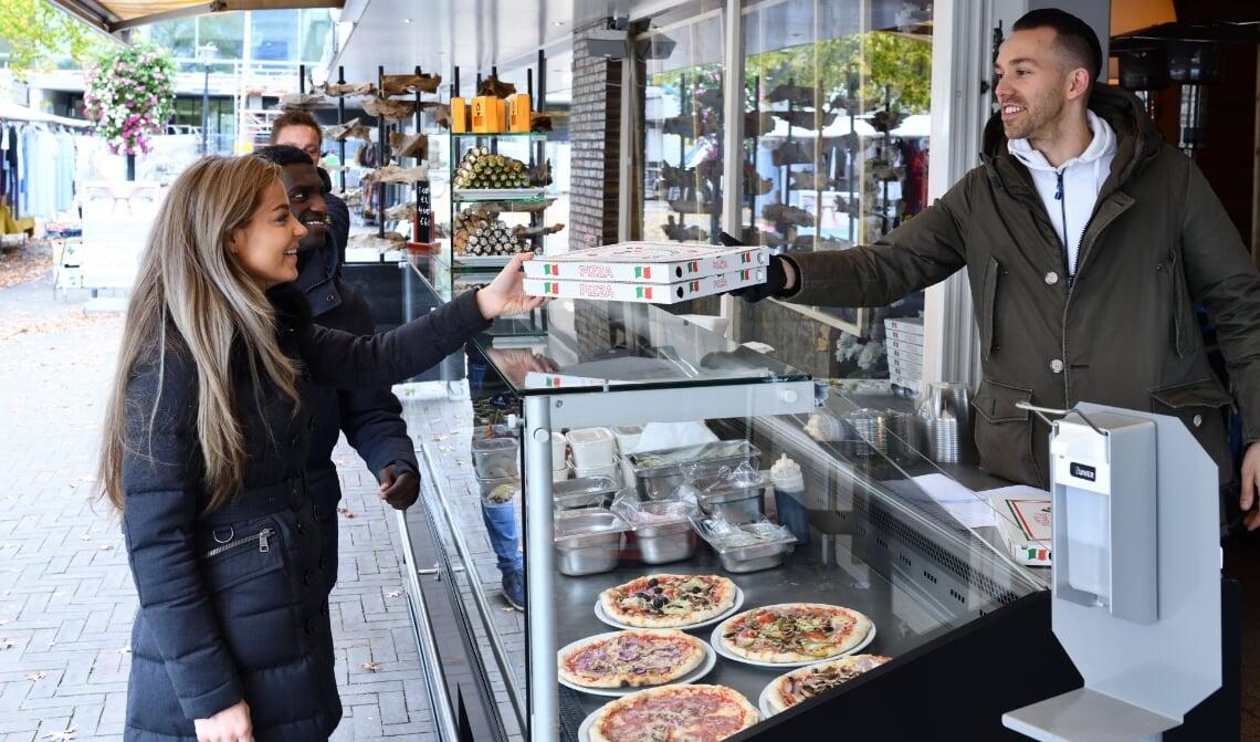 <p>Sander (r) verkoopt buiten vanuit zijn koeltoonbank verse gerechten</p>