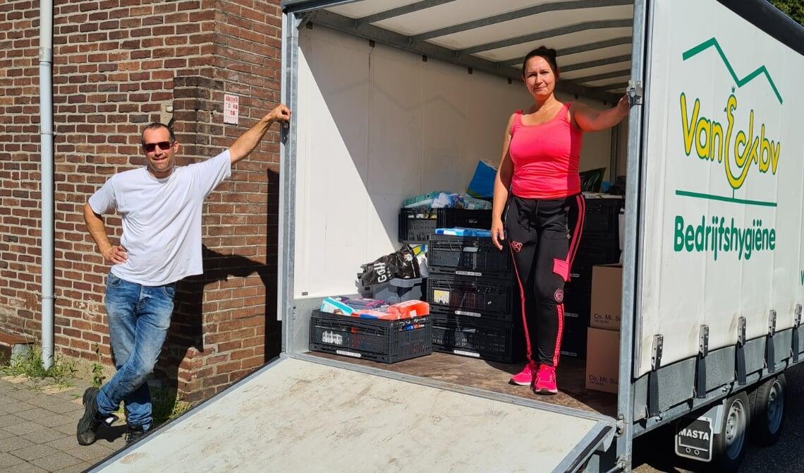 <p>Gilbert (l) en Sarah (r) bij de vrachtwagen die volgeladen werd met goederen voor Limburgers</p>