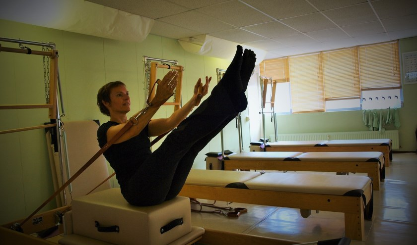 Sylvia Temmink demonstreert een pilates oefening op de Peak Pilates trainingsbank. Foto: Vsk