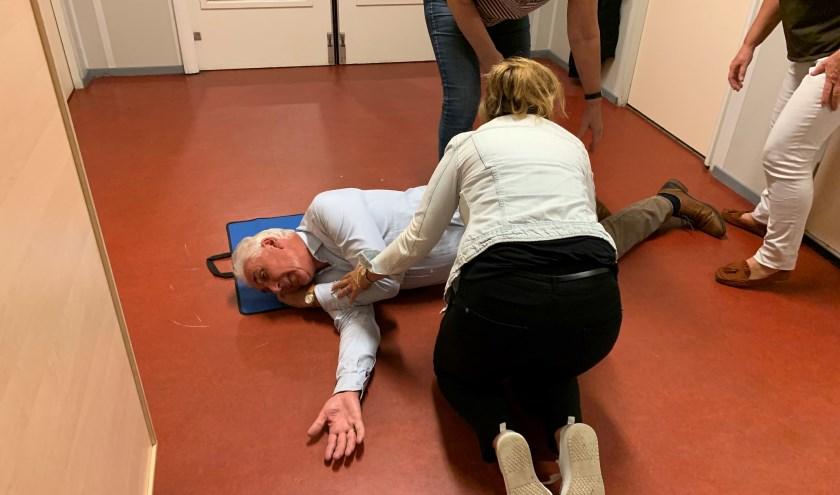 Fotohandelaar Hans van den Boogaardt toont zich een gewillig slachtoffer bij een demonstratie van een stabiele zijligging tijdens een reanimatiecursus voor Voorschotense bedrijven (Foto: Jasper Suijten)