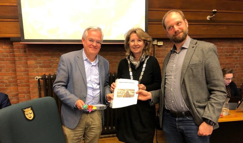 Erik Maassen van de SP heeft de uitkomsten van de enquête in de gemeenteraad aangeboden aan wethouder Cramwinkel en burgemeester Bouvy. Foto: VSK