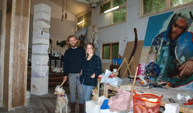 Kirsten Geerts en Joris Strouken met Flip.in hun atelier in de voormalige kapel op de buitenplaats Beresteyn. Het schilderij rechts is van Joris en de zuil links is het werk van Kirsten. Foto: Vsk Foto:  © VSK