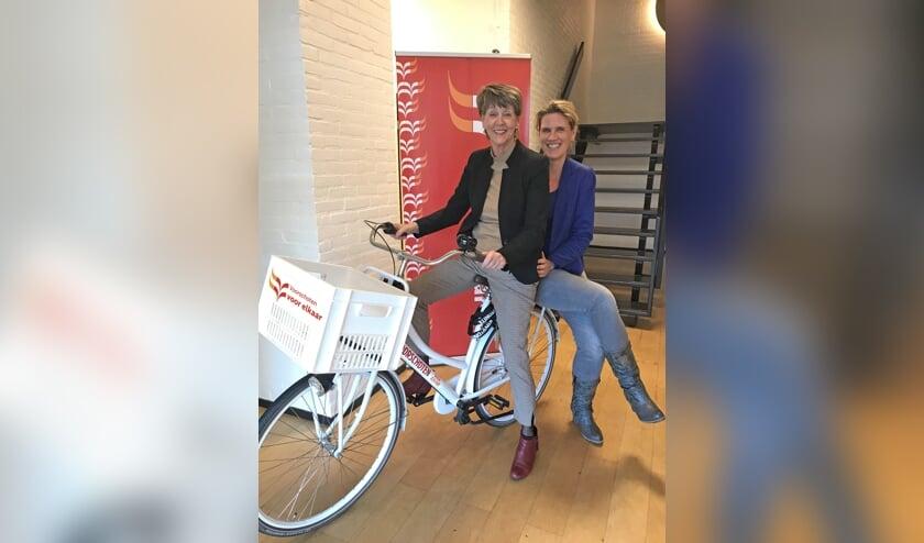 Ria van Vliet (l) vertrekt als directeur-bestuurder van Voorschoten Voor Elkaar. Haar opvolger Yvonne van Balen zit achterop. Foto: Voorschoten Voor Elkaar