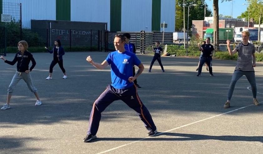 Taekwondo jeugdtraining op teerveldje achter de sporthal de Vliethorst