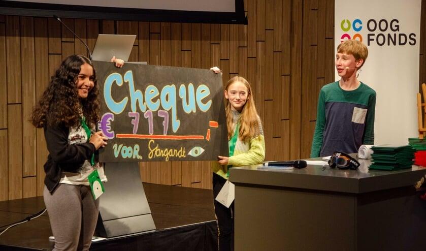 <p>Corn&eacute; krijgt van zijn klasgenootjes de cheque overhandigd. Alles gaat naar het Oogfonds voor onderzoek. Foto: Oogfonds</p>