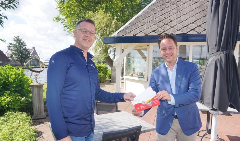 <p>Marcel van Teijlingen (l) van Restaurant De Knip ontvangt als eerste de Voorschotense Voordeel Horecabonnen van wethouder Paul de Bruijn.&nbsp;</p>