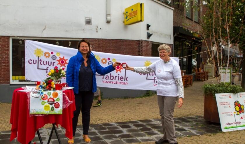 <p>Burgemeester Nadine Stemerdink (links) ontvangt Cultuurfabriek gietertje uit handen van Maria Huijts (rechts) (foto: Cultuurfabriek Voorschoten)</p>
