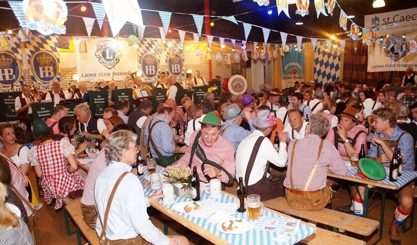 Impressie van het feest met de traditioneel verklede gasten aan lange tafels met bierpullen en Bratwurst (foto: pr).