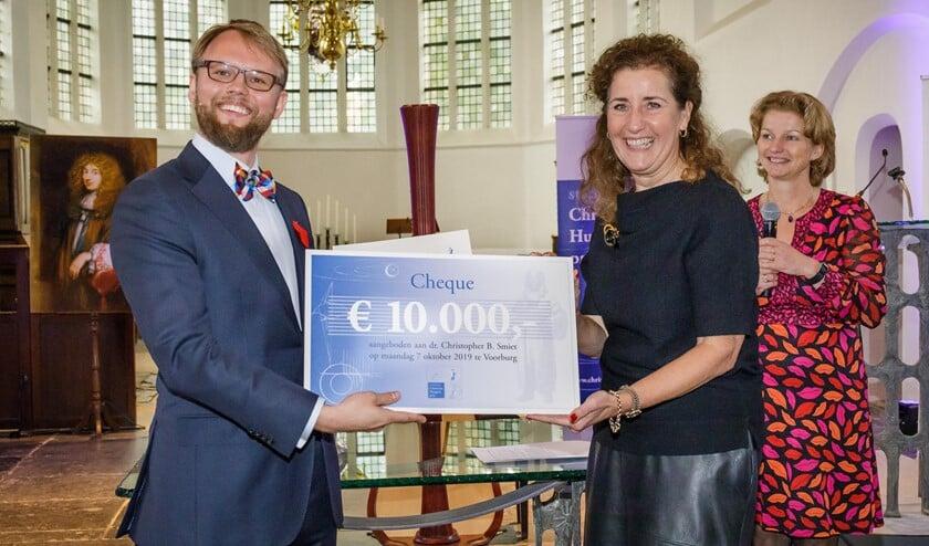 Fotobijschrift: Chris Smiet ontvangt de cheque behorend bij de Christiaan Huygens wetenschapsprijs 2019 uit handen van minister Ingrid van Engelshoven van OCW. Rechts de voorzitter van de Stichting Christiaan Huygensprijs, Marjan van Loon.