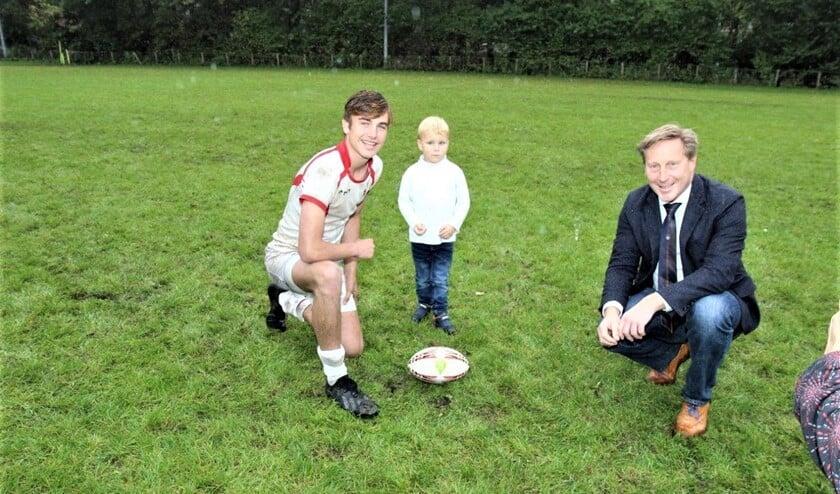 Om het veld officieel te openen namen de oudste en de jongste speler samen een kick op de palen (foto: Ap de Heus).