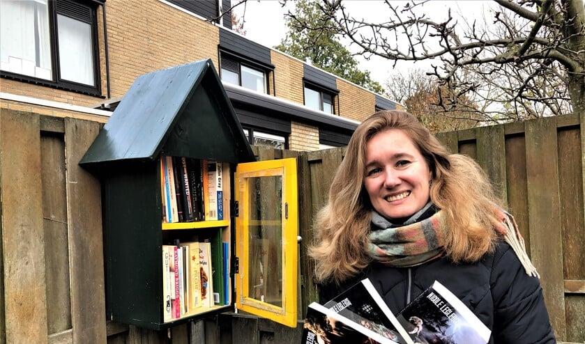 Nicole Leclercq bij de minibieb in Essesteijn met de door haar geschreven trilogie.