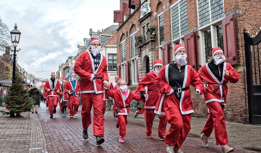 Kinderen en volwassenen rennen als kerstmannen door het Huygenskwartier (archieffoto Michel Groen).