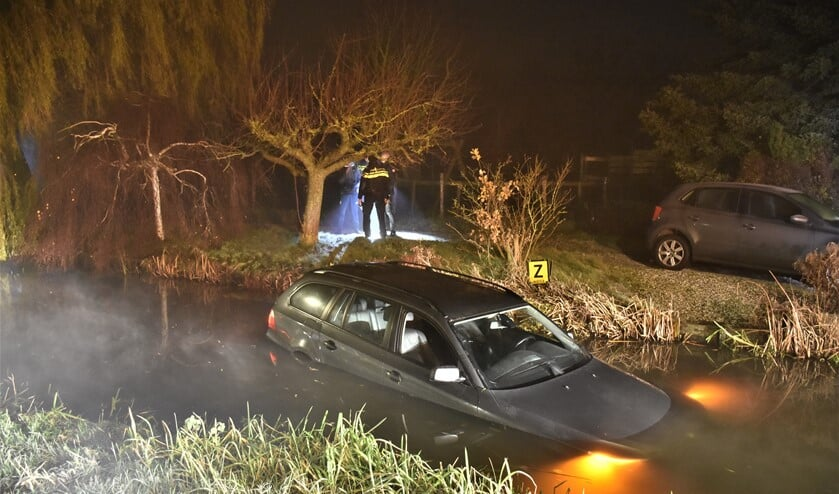 De personenauto drijft in afwachting van de berger nog enigszins rond in de sloot aan het Wilsveen in Leidschendam (foto: Sebastiaan Barel).