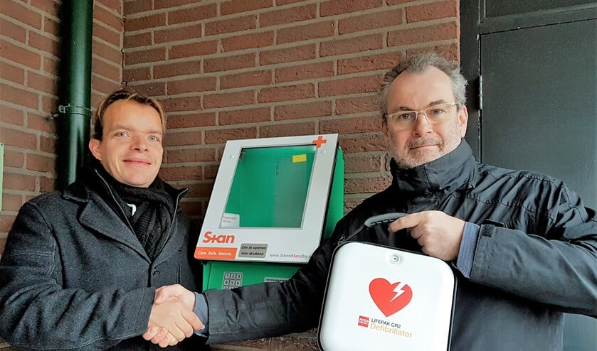 Wouter Verbeek van RLT Nederland (l.) en Adrey Caljé van het bestuur van VvE De Populier met de AED (foto: pr).