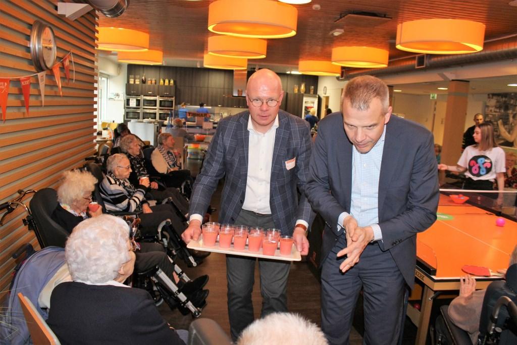 Burgemeester Klaas Tigelaar gaat bij WZH Het Anker rond met een lekker drankje (foto: DJ).  © Het Krantje