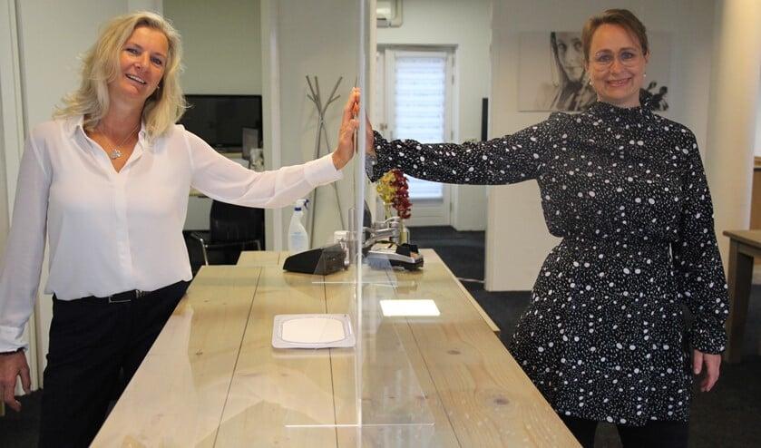 Dorothea en Eline bij het plexiglascherm dat bij de balie voor veiligheid zorgt.