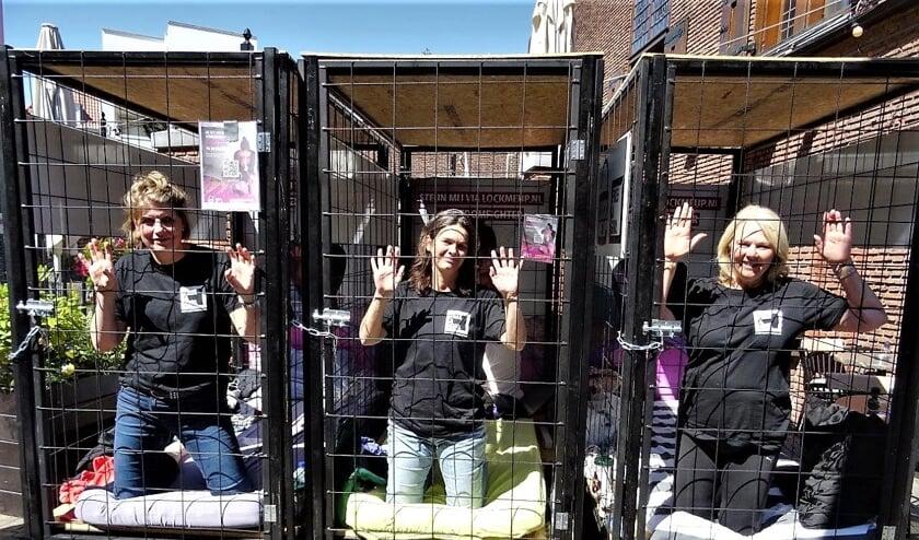 De dames die zich voor de actie 'Lock me Up – Free a Girl' lieten opsluiten in kleine hokjes (foto: Ap de Heus).