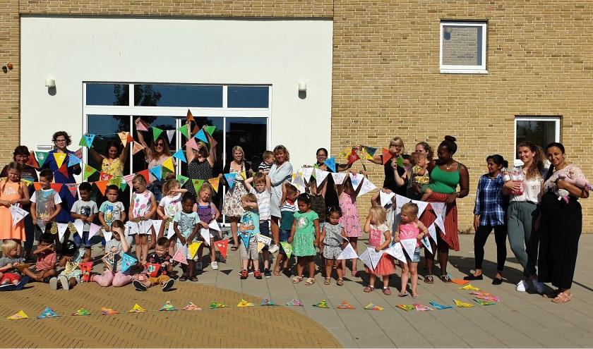 De kinderen zijn trots op hun mooi versierde vlaggetjes van de feestslinger. Foto: pr