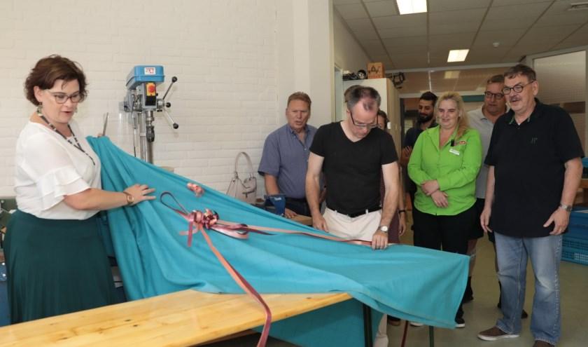 Wethouder Jakobien Groeneveld onthult een van de door de houtwerkplaats vanPiëzo opgeknapte meubelen. Foto: Jan van Es
