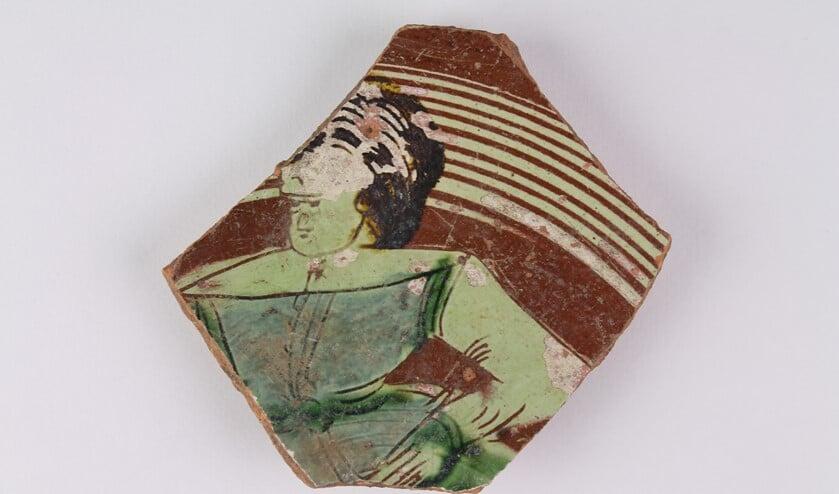 Dit fragment van een bord van aardewerk werd gevonden tijdens op de opgraving door de AWLV op de hoek van de Herenstraat en de Rozenboomlaan. De dame is gekleed volgens de mode van rond 1600, wat ook de periode is waarin dit aardewerk is gemaakt.