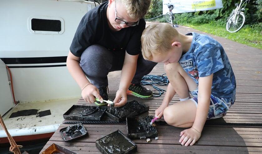 Met een tandenborstel maken de jongens de sieraden schoon. (Foto: Regio15/Donny Kooistra)