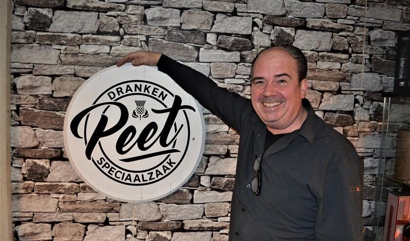 Peter Verbeek naast het nieuwe logo van zijn zaak  Drankenspeciaalzaak Peet.