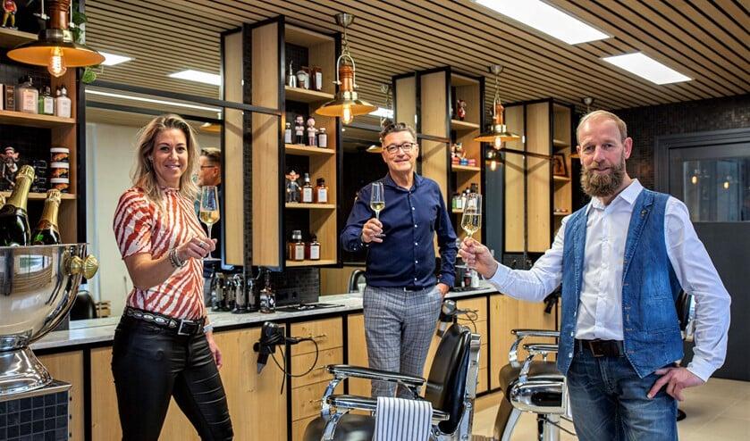 <p>Marco Rimmelzwaan (l.) en de andere teamleden proosten op de heropening van de zaak (foto: Harry Scholtes). </p>