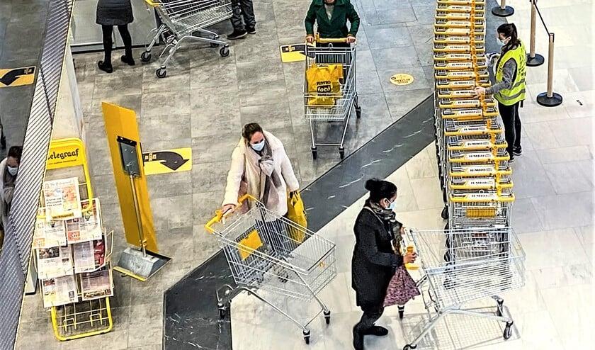 <p>Mondkapjes op, afstand houden en winkelwagentjes schoonmaken, een tijdsbeeld<br>bij een supermarkt in winkelcentrum Leidsenhage (foto: Michel Groen).</p>