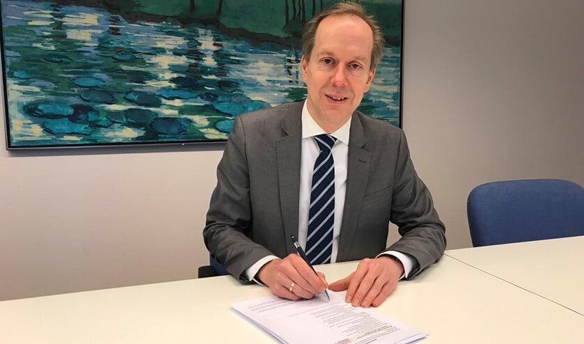 Wethouder Rouwendal tekent voor de verkoop van de aandelen, waarmee de gemeente zo'n 140 euro rijker wordt (foto: gemeente LDVB).