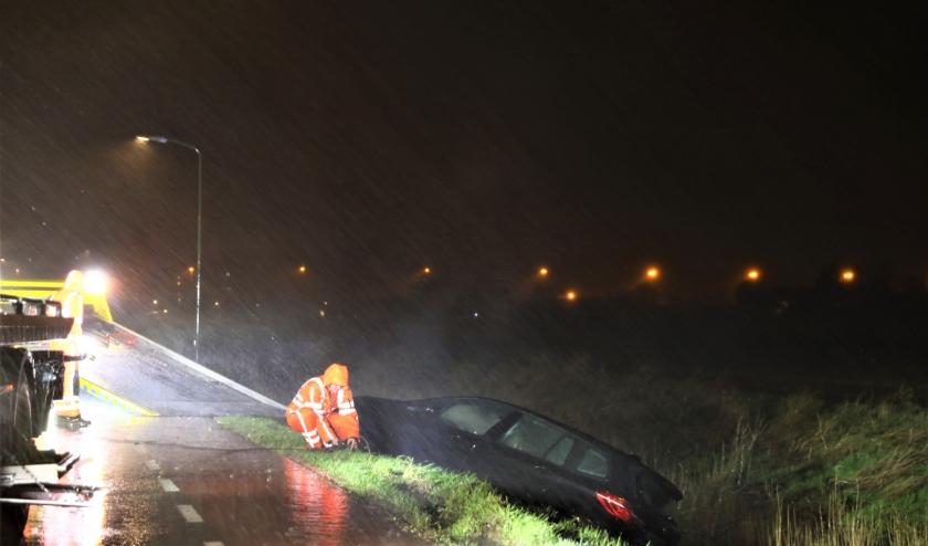 Tijdens het noodweer wordt de personenauto geborgen (foto: Sander Paardekooper).