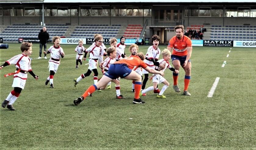 De rugby internationals worden belaagd door een horde jonge spelers van VCC (foto: Wietske de Jong).
