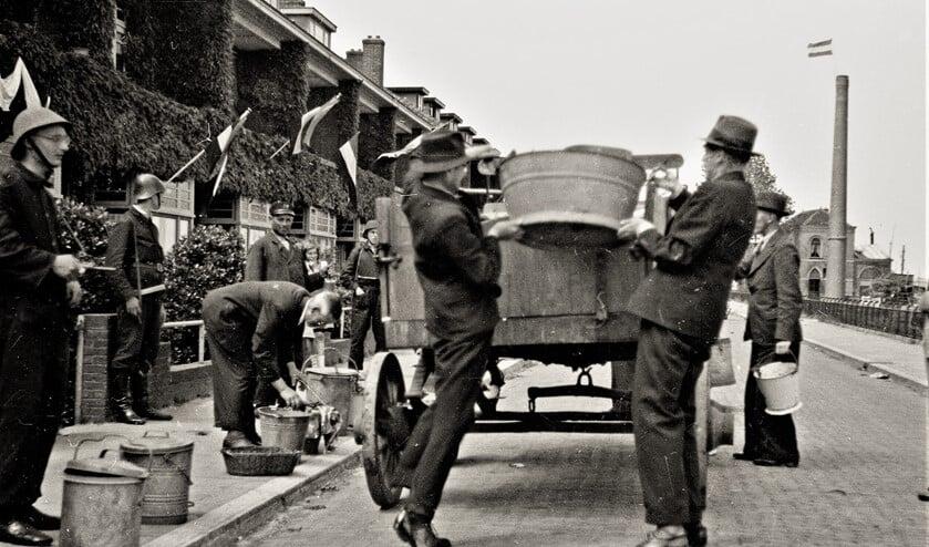 NSB-ers worden in mei 1945 door leden van de Binnenlandse Strijdkrachten verplicht om huisvuil op te halen (foto: Henk J. Janszen).