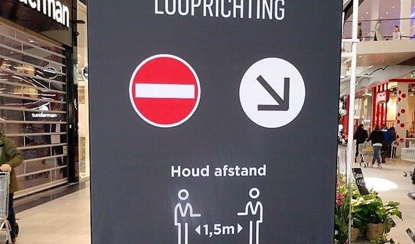 Bord in winkelcentrum Leidsenhage om mensen te wijzen op o.a. de looprichting en het houden van voldoende afstand (foto: Ap de Heus).