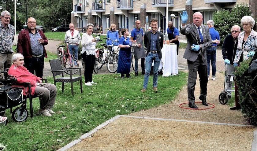 Burgemeester Klaas Tigelaar verricht de eerste worp op de nieuwe jeu-de-boulesbaan bij WZH Schoorwijck in Leidschendam (foto: Ot Douwes).