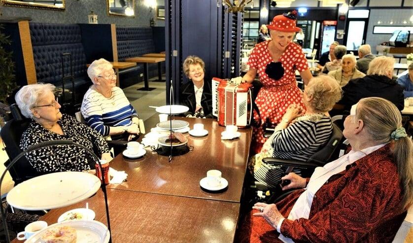 <p>&nbsp;Een clownesk aangeklede vrouw speelde op een accordeon liedjes waarbij bewoners konden meezingen (foto: Ap de Heus). </p>