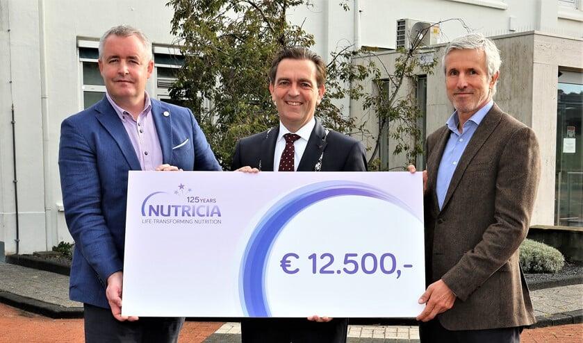 Burgemeester Bezuijen krijgt een cadeau van het jarige Nutricia. /Foto: Fred Roland