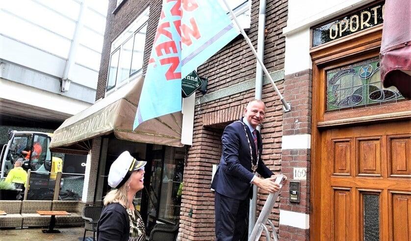 Burgemeester Jules Bijl hangt de vlag van de Kinderboekenweek op (foto: Ap de Heus).