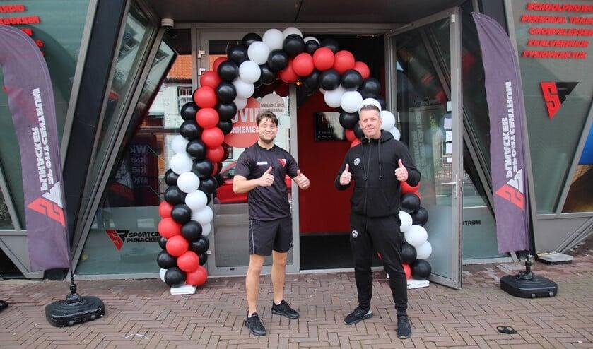 <p>Dave Nijhuis en zijn collega Gerald Lagrand onder de ballonnenboog bij de entree van Sportcentrum Pijnacker.</p>
