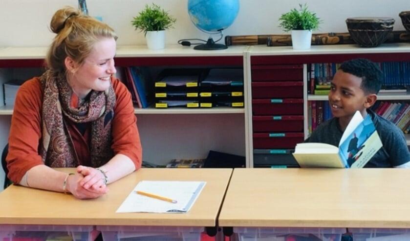 Een begeleider en leerling lezen samen een boek
