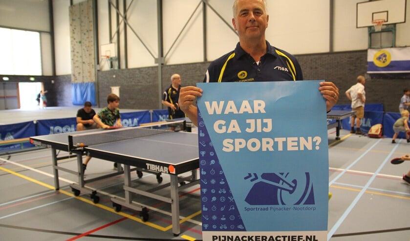 <p>Roel van der Beek tijdens de Sportmarkt in De Viergang met een poster die nu ook in de hele gemeente langs de weg te zien is.</p>