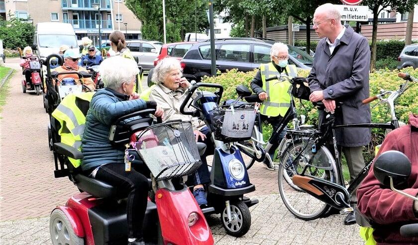 Start van de scootmobieltocht met deelnemers in gesprek met burgemeester Klaas Tigelaar (foto: Ot Douwes).
