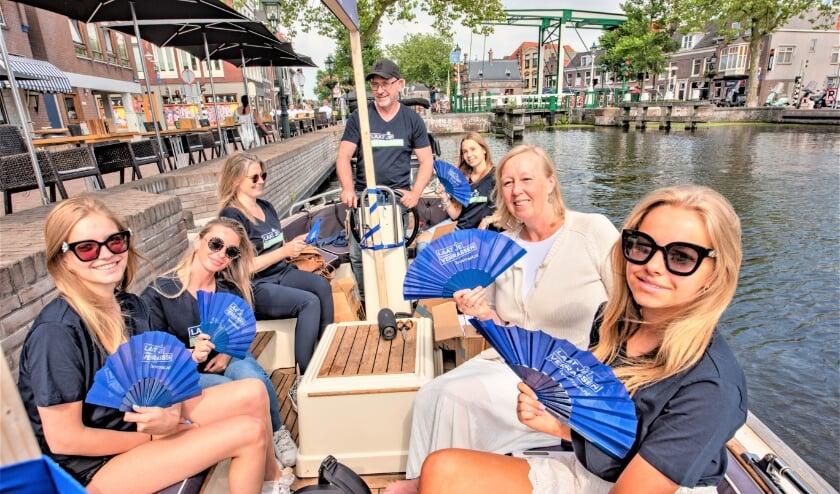 <p>Vanaf een boot deelde de wethouder waaiers uit (foto: gemeente LV).</p>