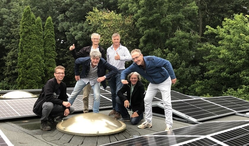<p>Het projectteam bewondert de zonnepanelen op het dak.</p>